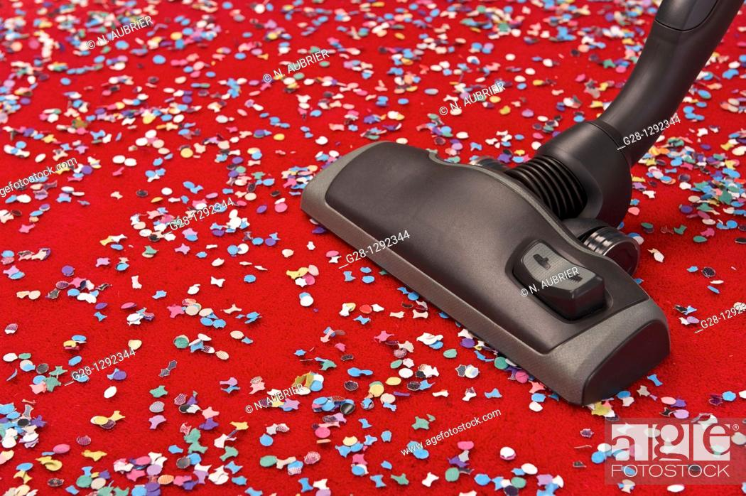 Imagen: Hoovering coloured confetti spread over a red carpet, concept image of removing dust, cleaning, suppressing pollution and allergy.