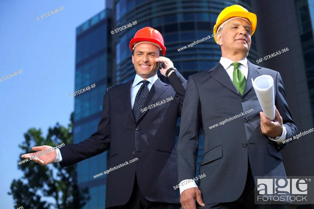 Stock Photo: Two businessman wearing hardhats.