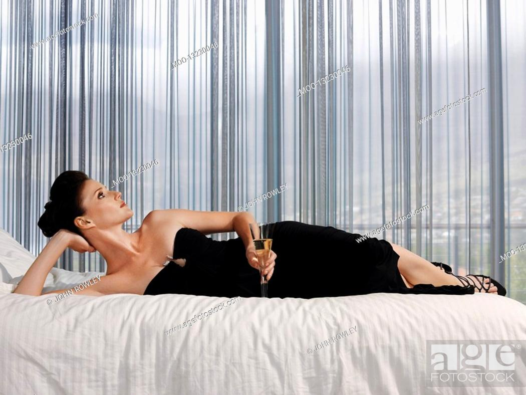 Stock Photo: Woman wearing elegant dress lying on bed with champagne glass in bedroom.