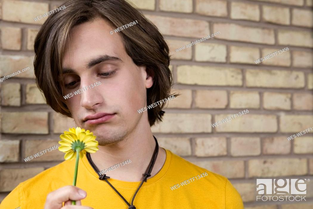Stock Photo: Germany, Berlin, Young man in front of brick wall holding flower, portrait, close-up.