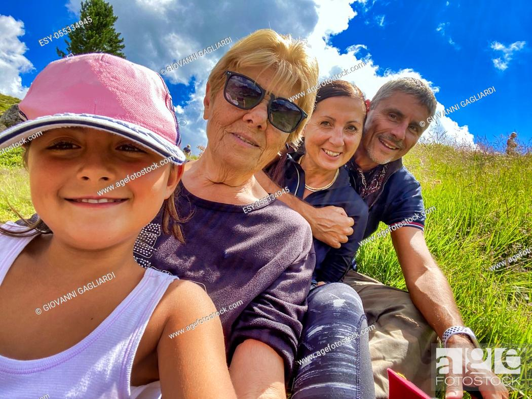 Photo de stock: Three generations female with a man on a mountain excursion.