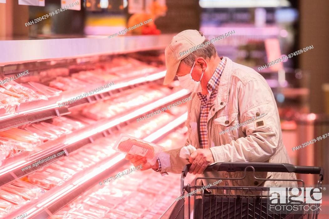 Stock Photo: 29 April 2020, North Rhine-Westphalia, Duesseldorf: A customer with a mouth and nose protector shops at Edeka Zurheide. Photo: Rolf Vennenbernd/dpa.