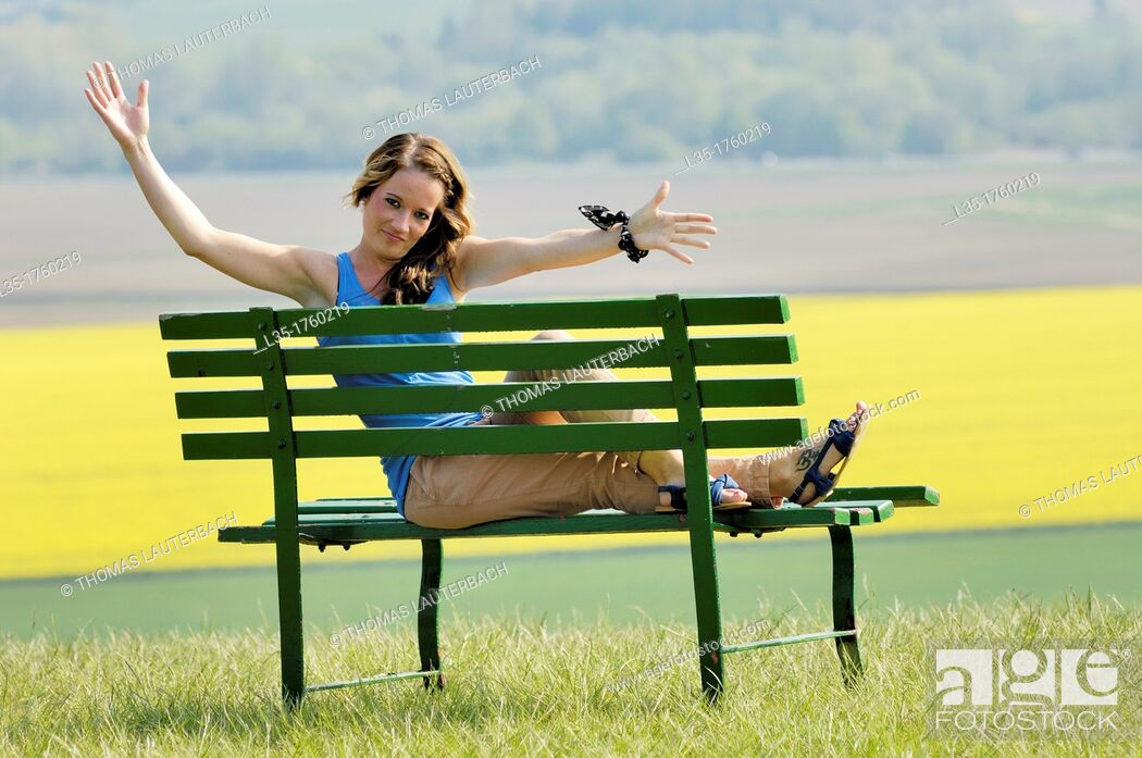 Stock Photo: Young woman sitting on bench.
