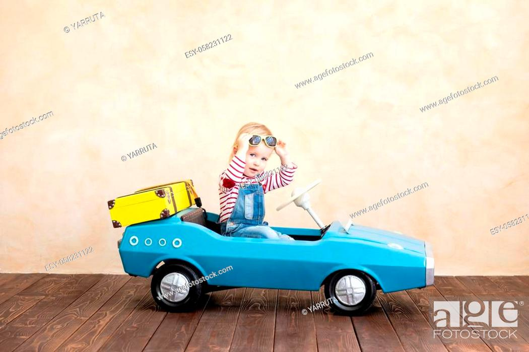 Stock Photo: Happy child riding toy vintage car. Funny kid playing at home. Summer vacation and travel concept.