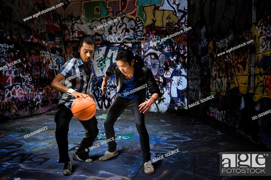 Stock Photo: Two men playing basketball.