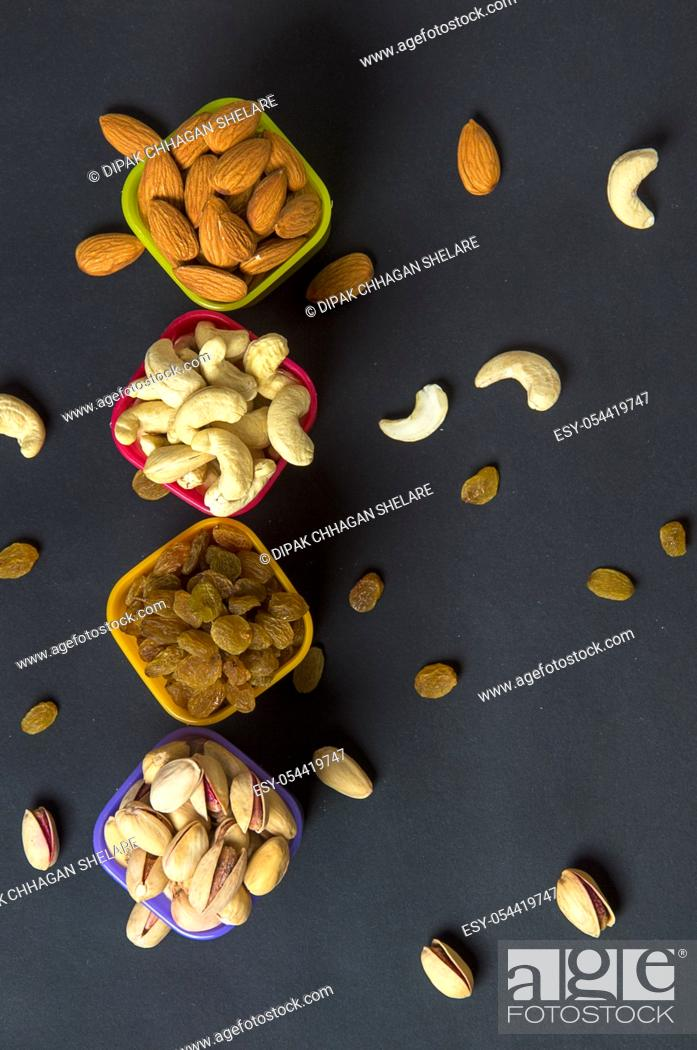 Stock Photo: Healthy Mix Dry Fruits and Nuts on dark background. Almonds, Pistachio, Cashews, Raisins.