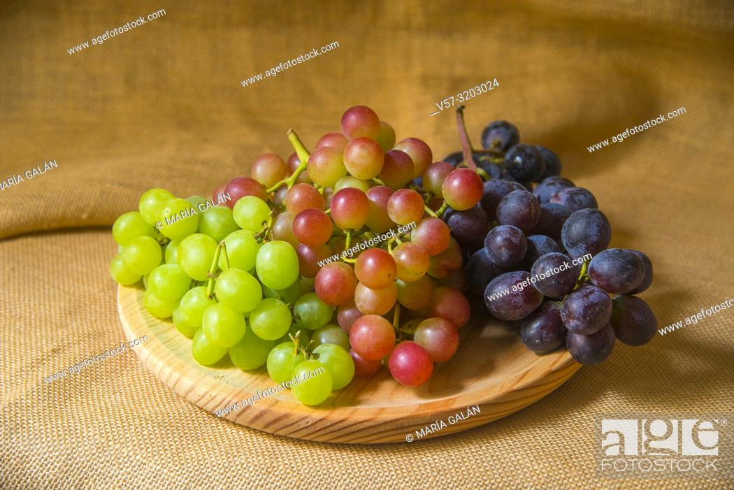 Stock Photo: Bunches of three colors grapes on wooden dish.