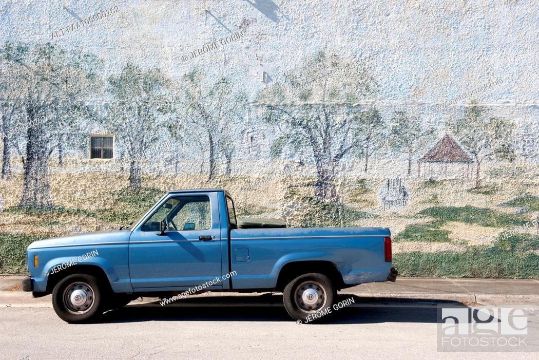 Stock Photo: Pick-up truck parked beside wall with mural painted on it.