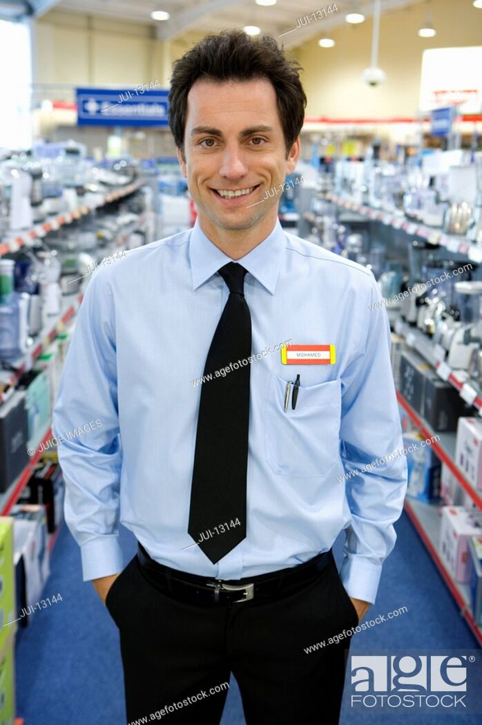 Stock Photo: Young salesman in electronics aisle, hands in pockets, smiling, porttrait.