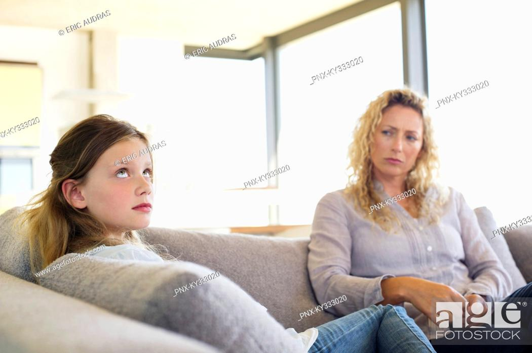Stock Photo: Mid adult woman and her daughter sitting on a couch.