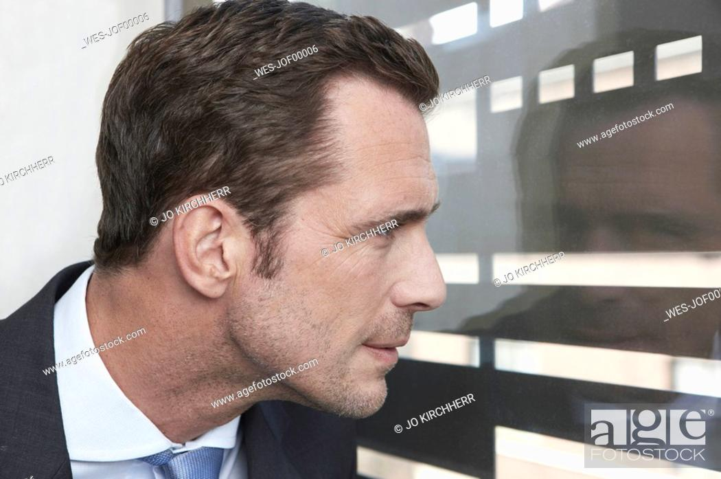 Stock Photo: Germany, Cologne, Businessman looking through window, side view, portrait, close-up.