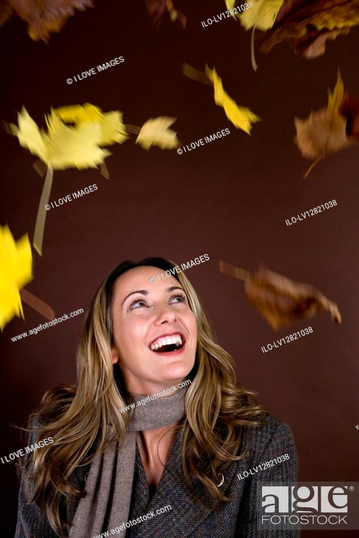 Stock Photo: A mid adult woman smiling at falling autumn leaves.