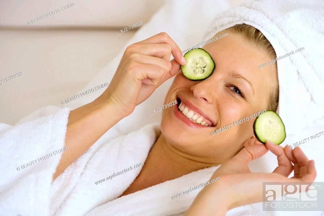 Stock Photo: Woman smiling with cucumber on her eyes.