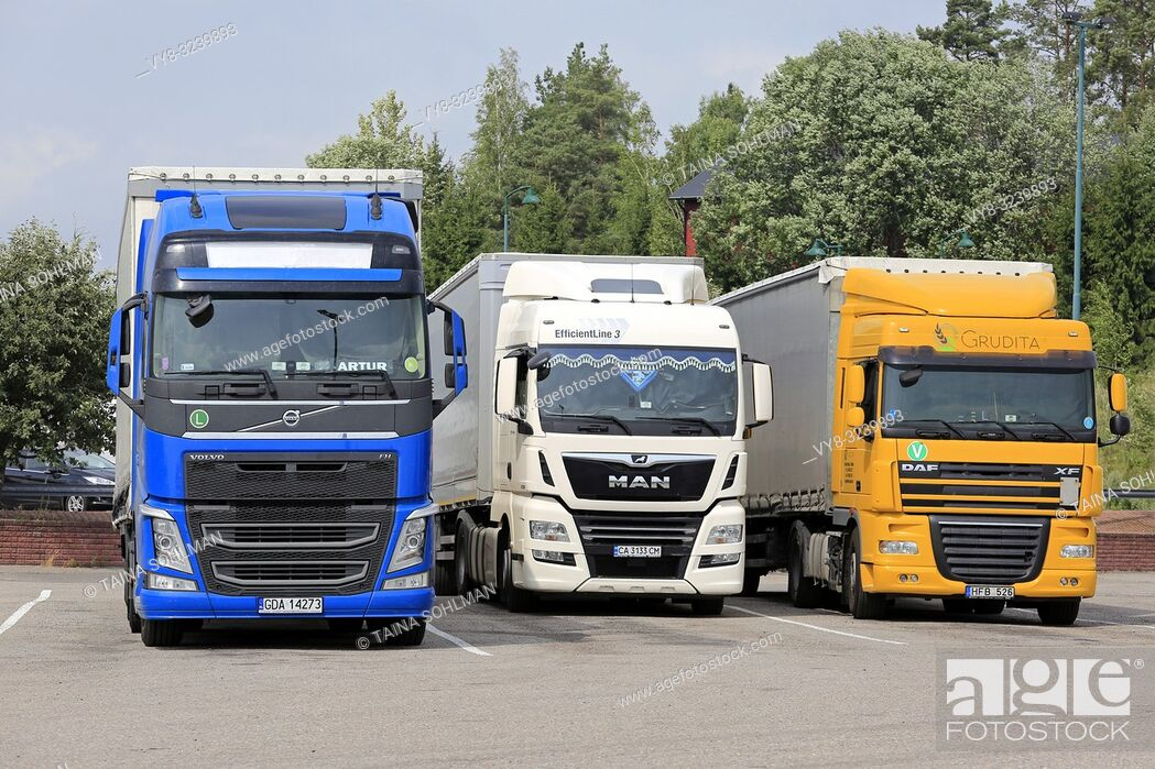 Stock Photo: Salo, Finland - July 29, 2018: Volvo FH, MAN and DAF XF transport trucks from Poland, Ukraine and Lithuania parked on a Finnish truck stop in summer.