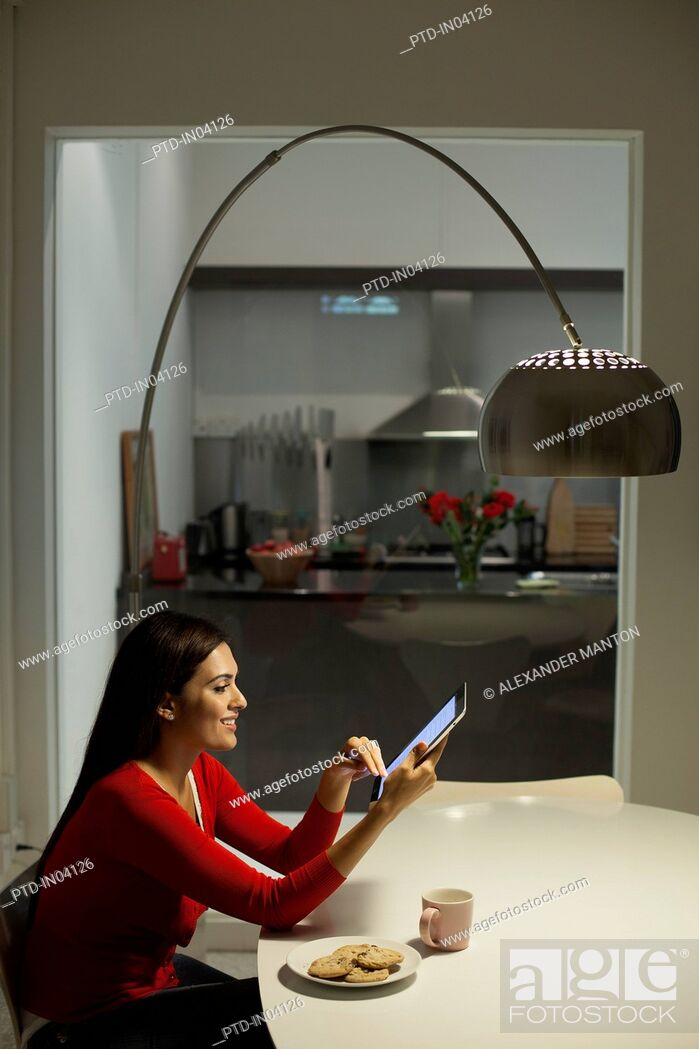 Stock Photo: Singapore, Young woman using tablet pc in dining room at night.