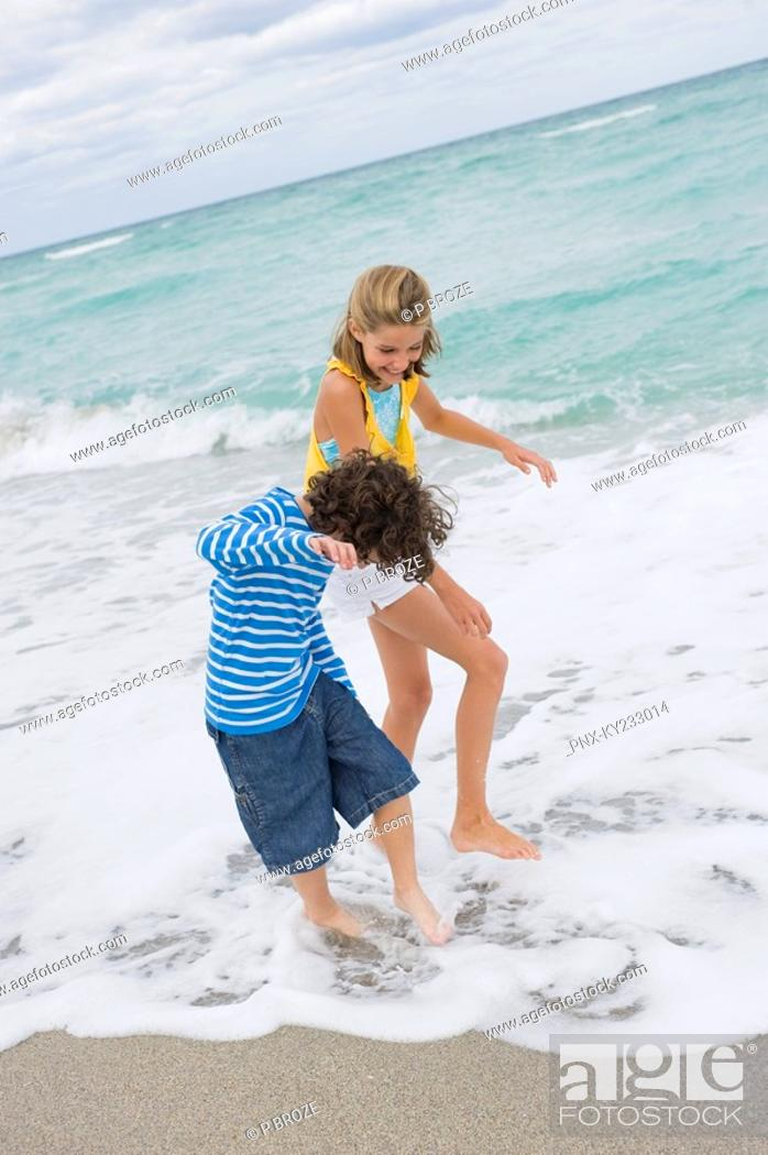 Stock Photo: Boy playing with a girl on the beach.