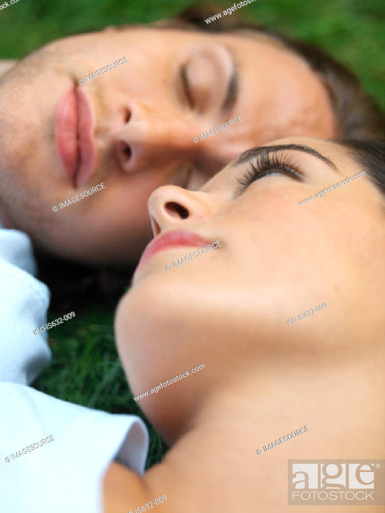 Stock Photo: Young couple sleeping in field.