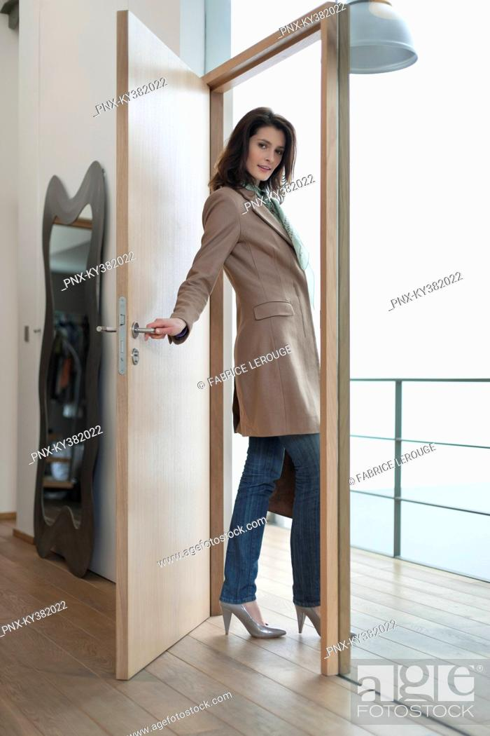 Stock Photo: Woman closing the door of a house.