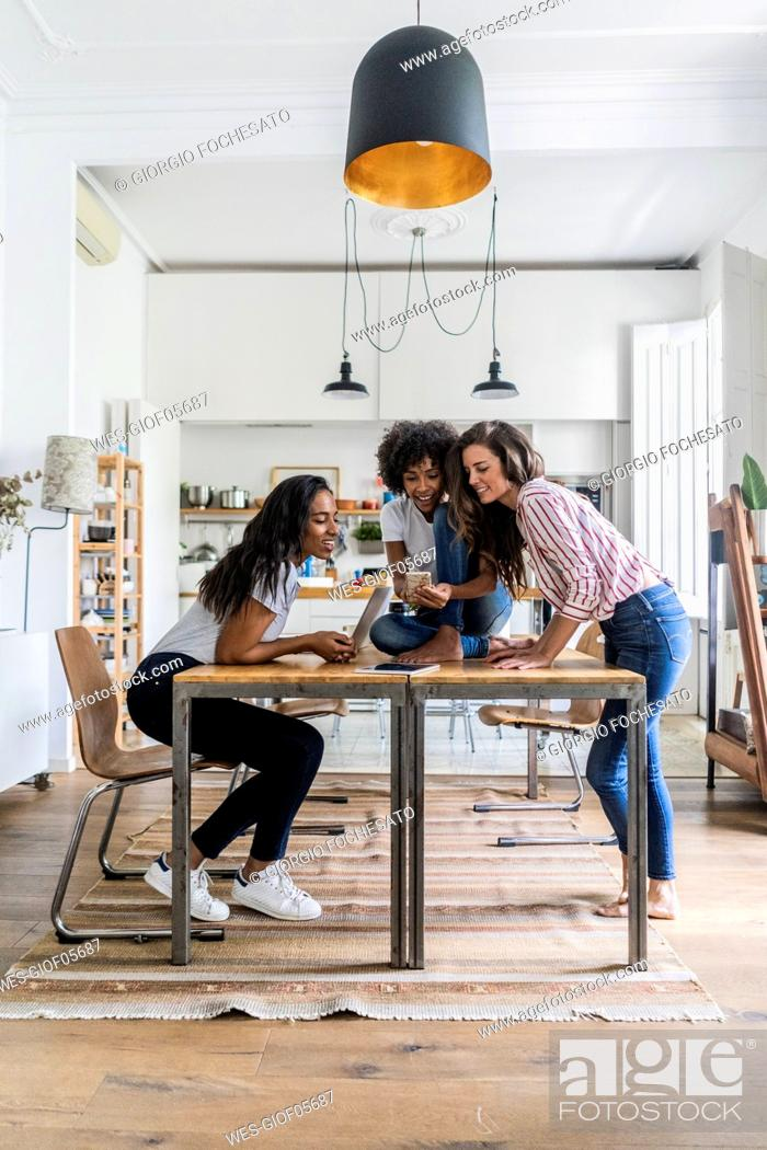 Stock Photo: Three happy women with digital devices on table at home.
