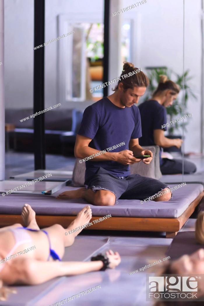 Stock Photo: Young man with phone in yoga class.
