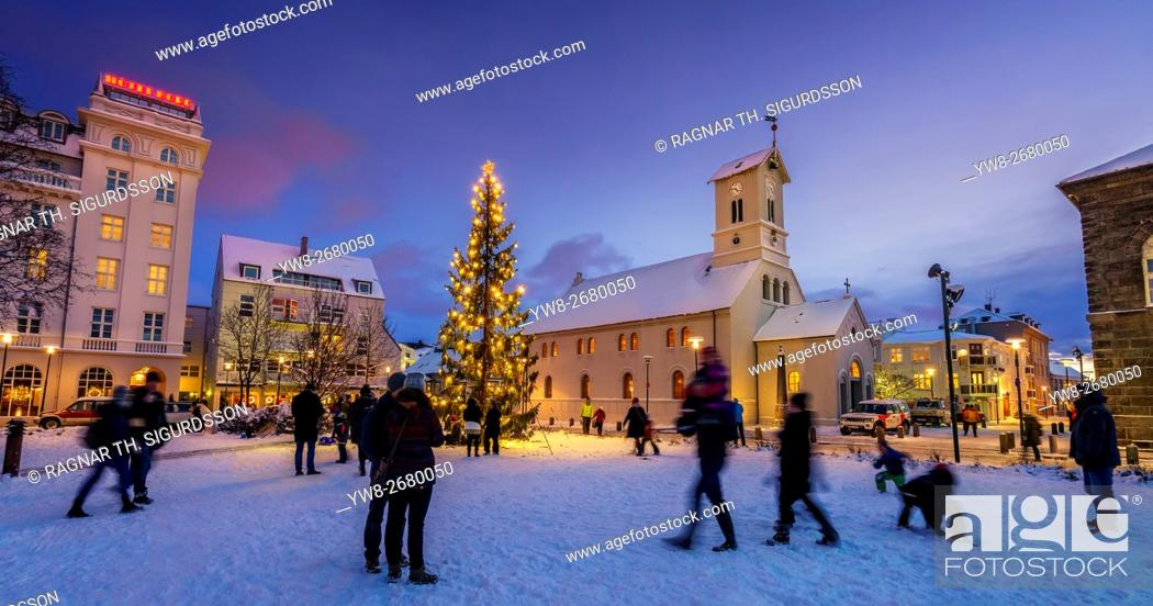 Stock Photo: Christmas tree and Domkirkjan Church. People enjoying a winter evening in downtown, Reykjavik during Christmas time, Iceland.