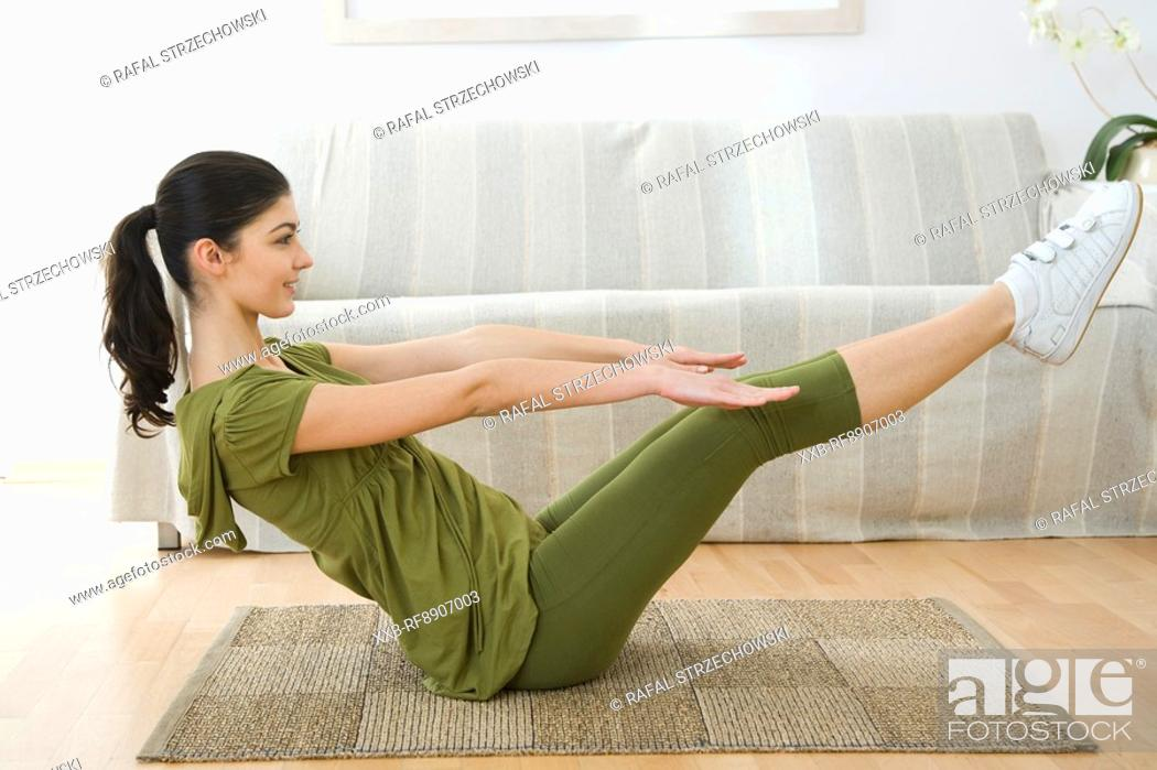 Stock Photo: young woman doing sit-ups.