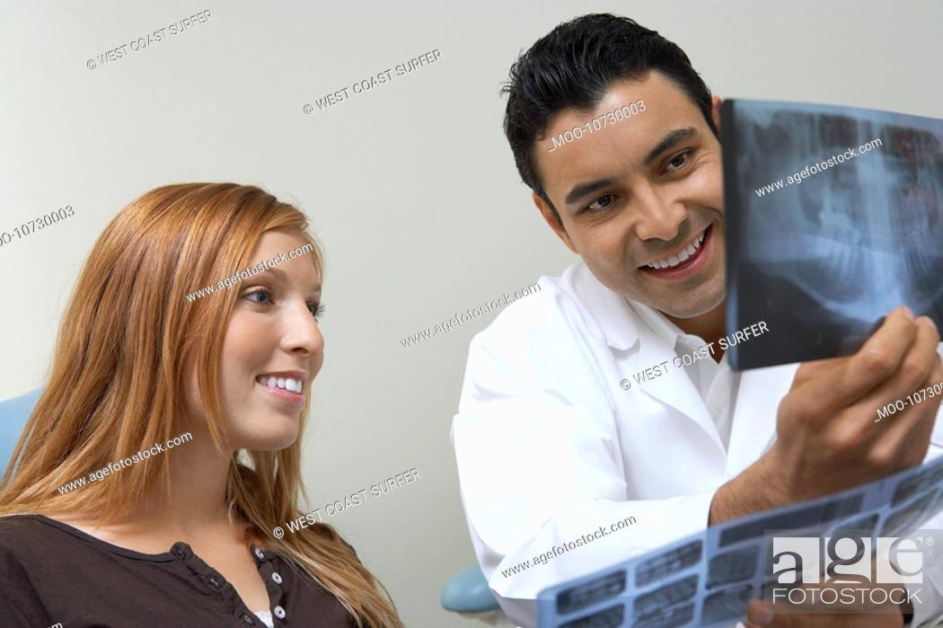 Stock Photo: Dentist and patient examining X-rays.