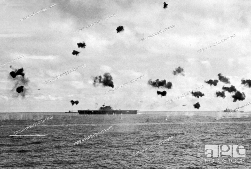 Stock Photo: Midway Island, Pacific Ocean: June, 1942 Low flying Japanese torpedo planes come in from the right flying amidst bursting anti-aircraft shells as they aim for a.
