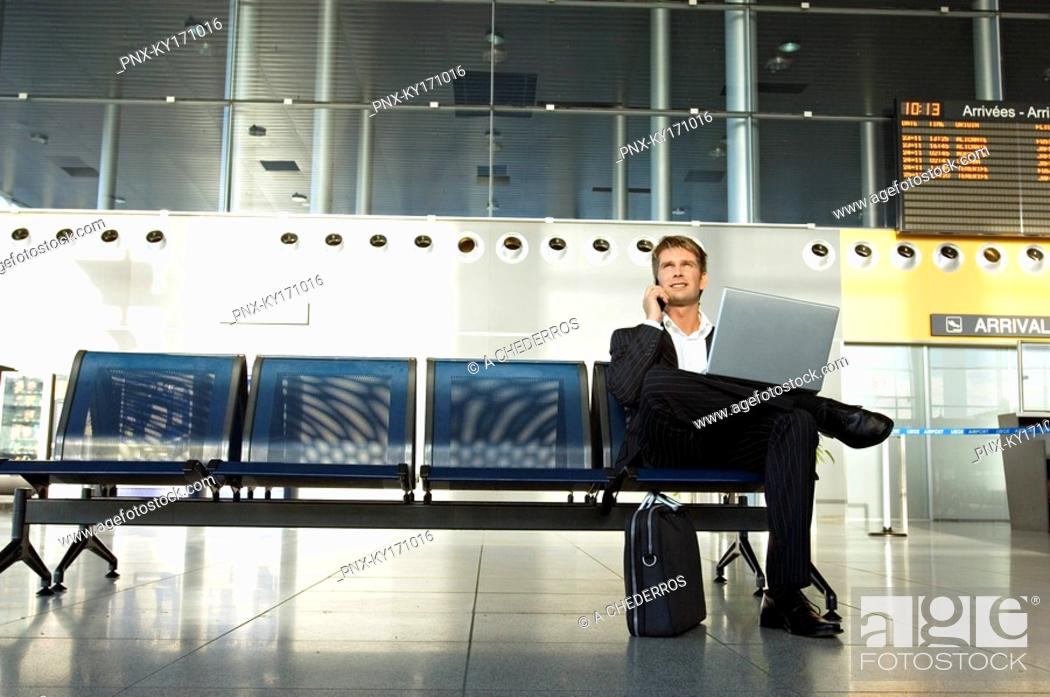 Stock Photo: Businessman using a laptop and talking on a mobile phone.
