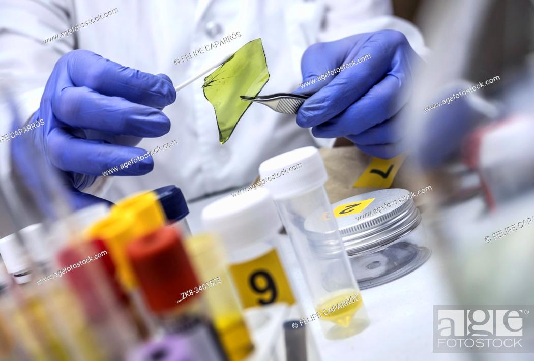 Stock Photo: Police expert gets blood sample from glass bottle in Criminalistic Lab.