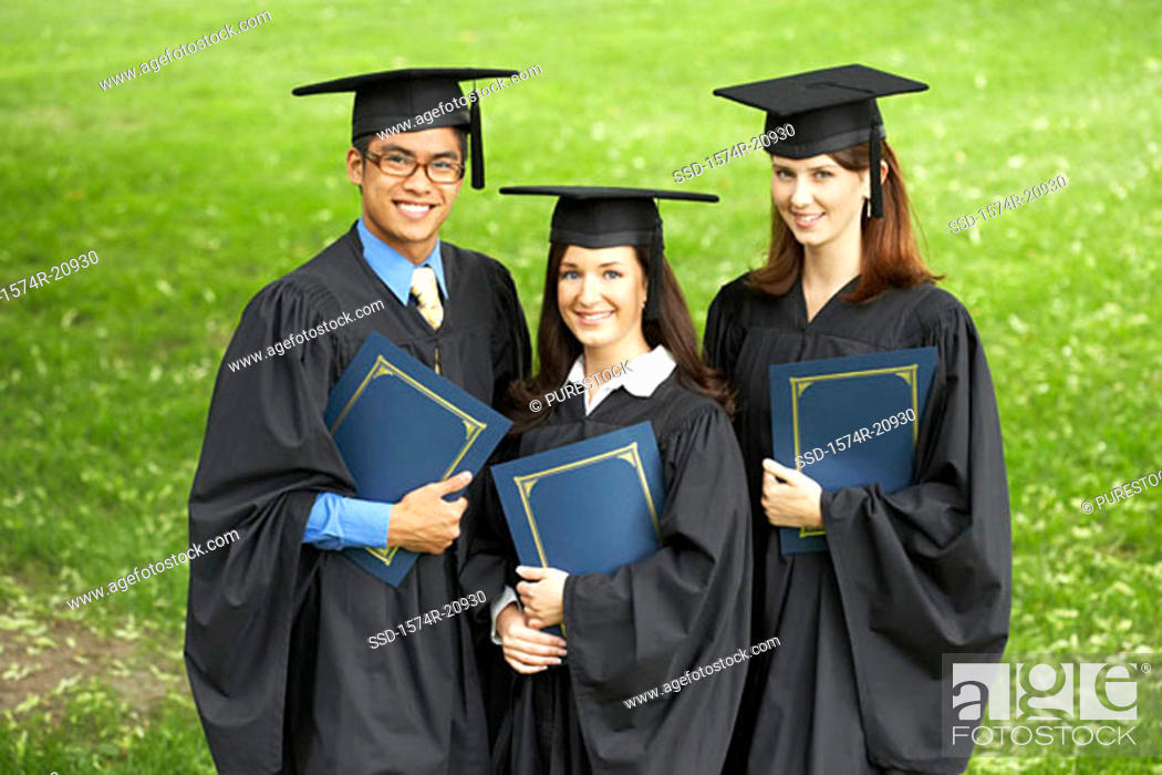 Stock Photo: Portrait of two female graduates and a male graduate holding files.