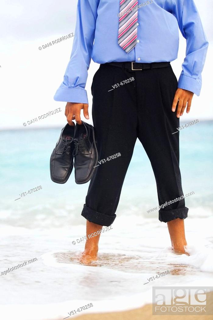 Stock Photo: Barefoot businessman standing by the sea.