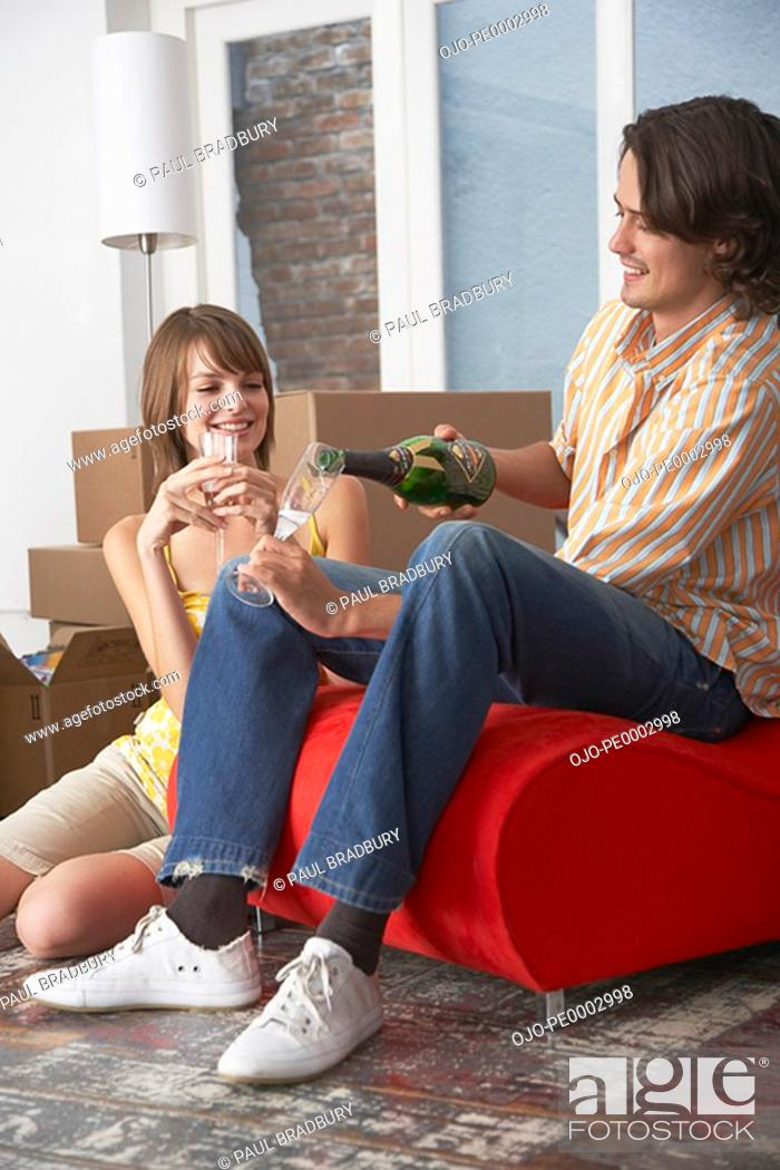 Stock Photo: Couple with champagne in house with red chair celebrating.