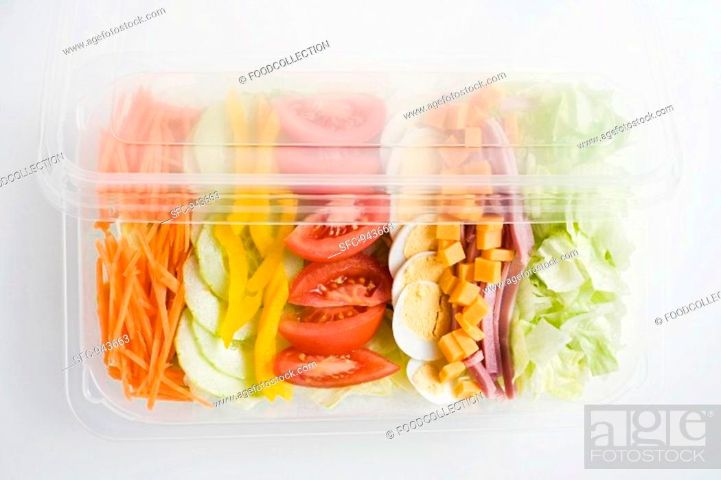 Stock Photo: Mixed salad with ham and egg in a plastic tray.