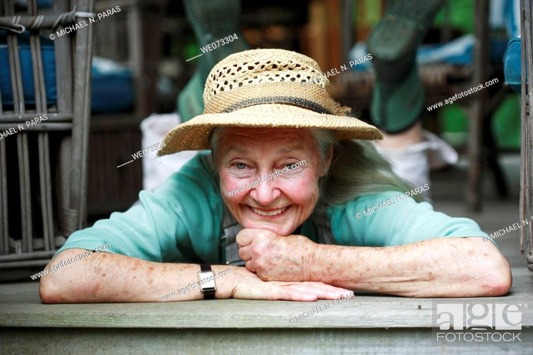 Stock Photo: Senior woman with straw hat laying on stomach looking into camera smiling.