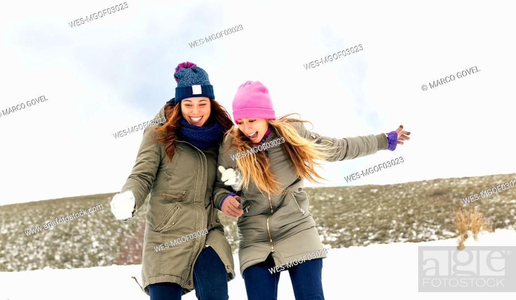 Stock Photo: Two friends having fun in the snow.
