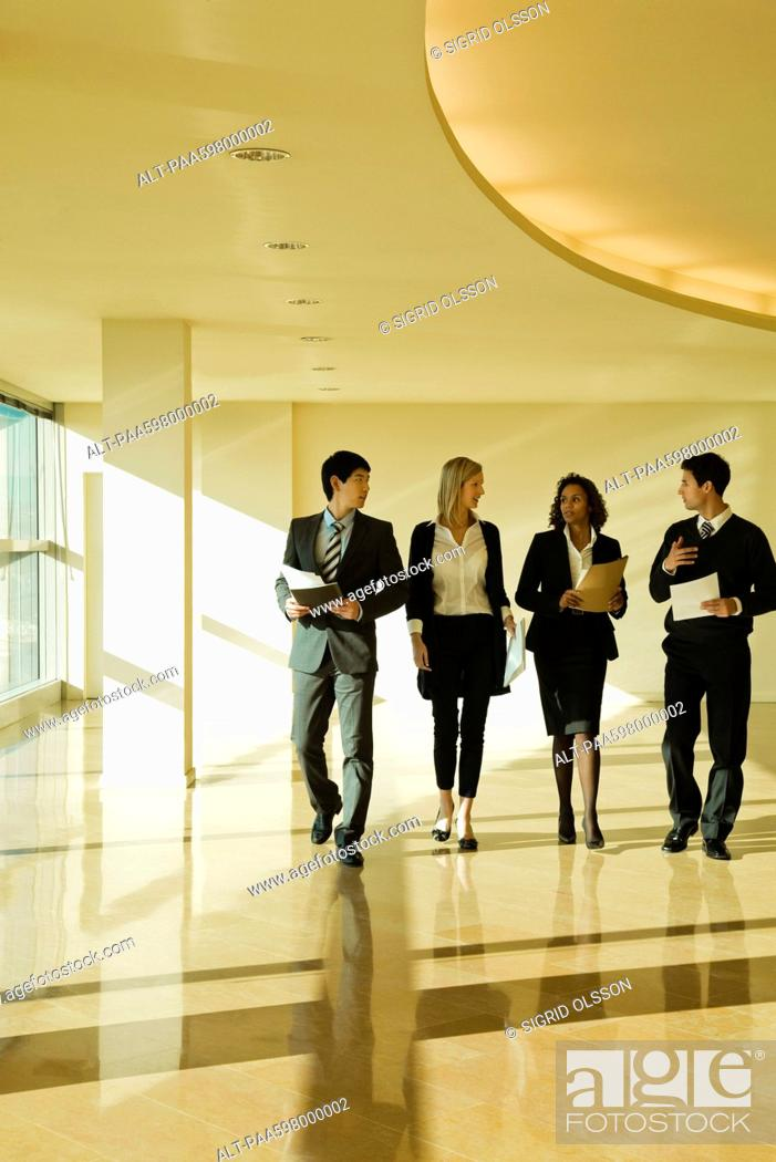 Stock Photo: Group of executives talking as they walk together in lobby.