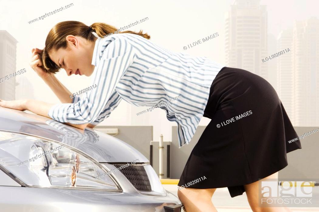 Stock Photo: A businesswoman leaning on the bonnet of a car.
