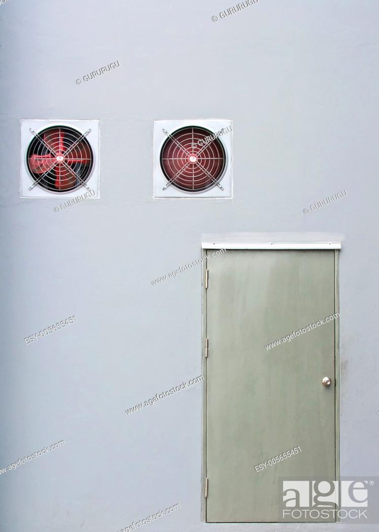 Stock Photo: A pair of red industrial ventilated fan on grey wall with a stainless steel door as background.