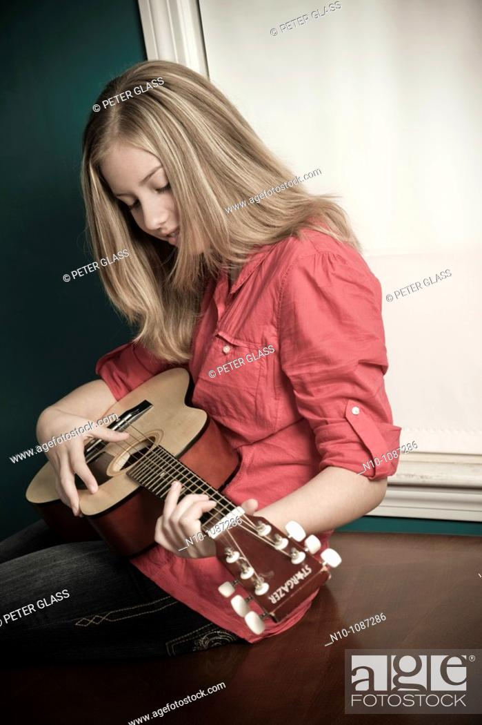Stock Photo: Blond preteen girl playing a guitar.
