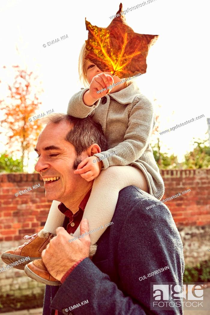 Stock Photo: Father carrying daughter on shoulders.