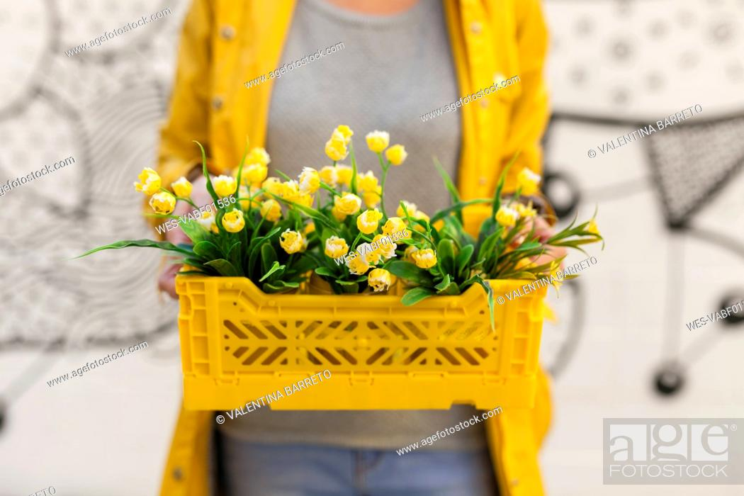 Stock Photo: Close-up of woman holding yellow spring flower box.