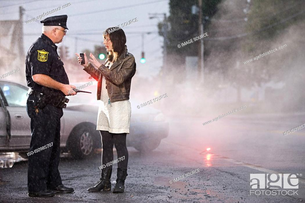 Stock Photo: Young woman and police officer at scene of crash.