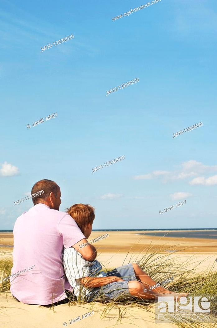 Stock Photo: Father and Son sitting on sand dune looking out on Beach back view.