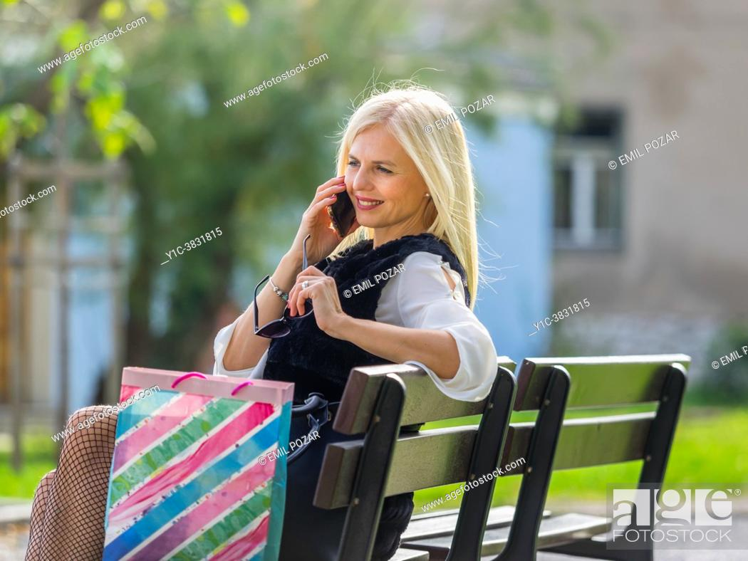 Stock Photo: Attractive shopper blonde in park with shopping bags smartphone conversation.