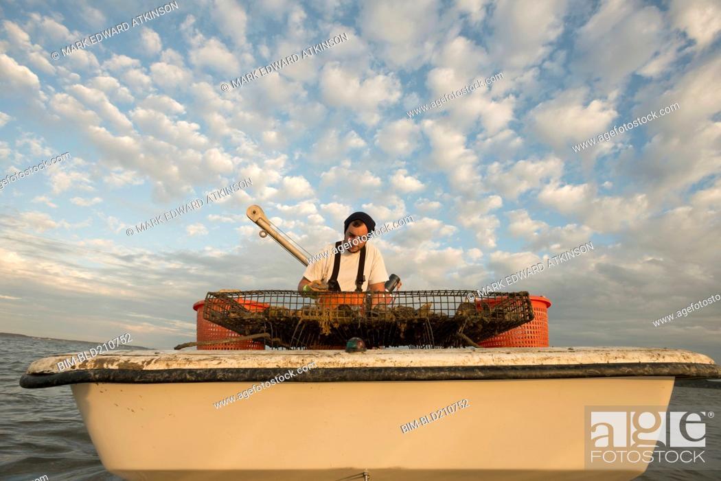 Stock Photo: Caucasian fisherman examining net on boat.