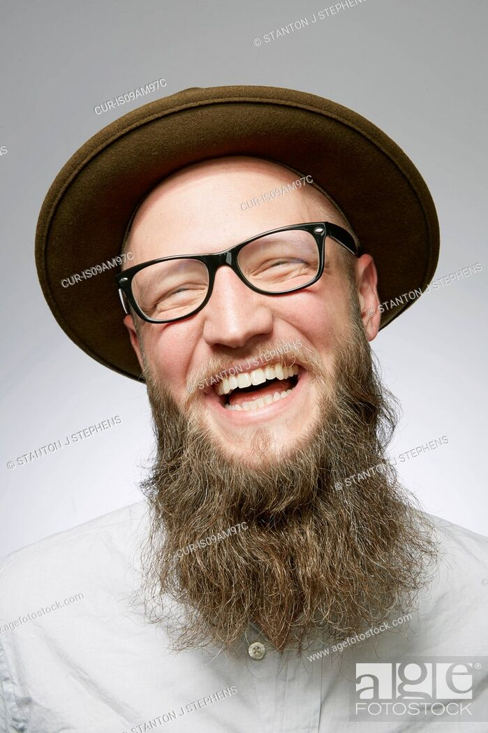 Stock Photo: Studio portrait of laughing mid adult man in trilby with overgrown beard.