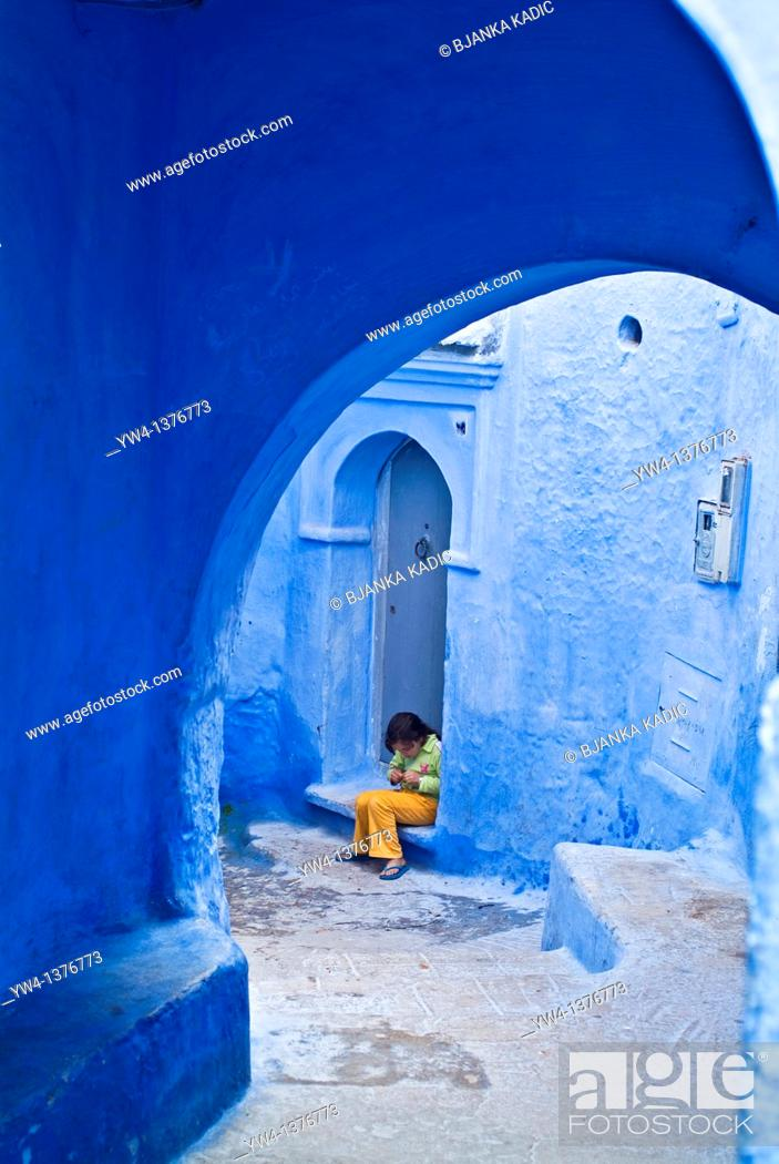 Stock Photo: Street scene with a girl sitting on a threshold of a house, Chefchaouen, Morocco.