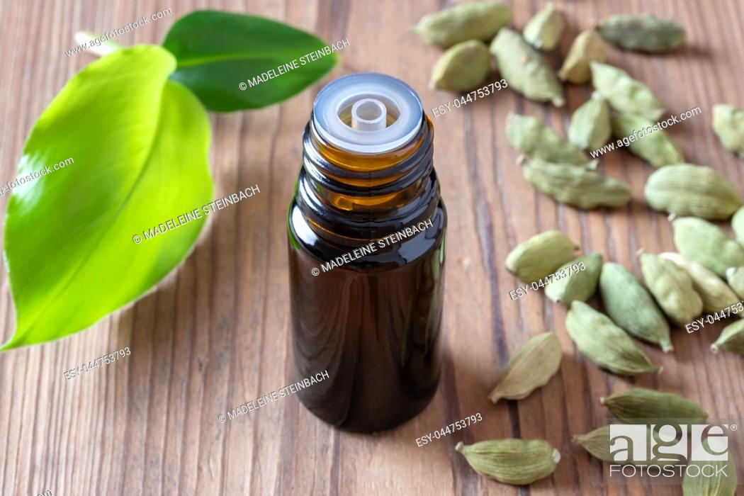 Stock Photo: A bottle of essential oil with cardamon pods and leaves.