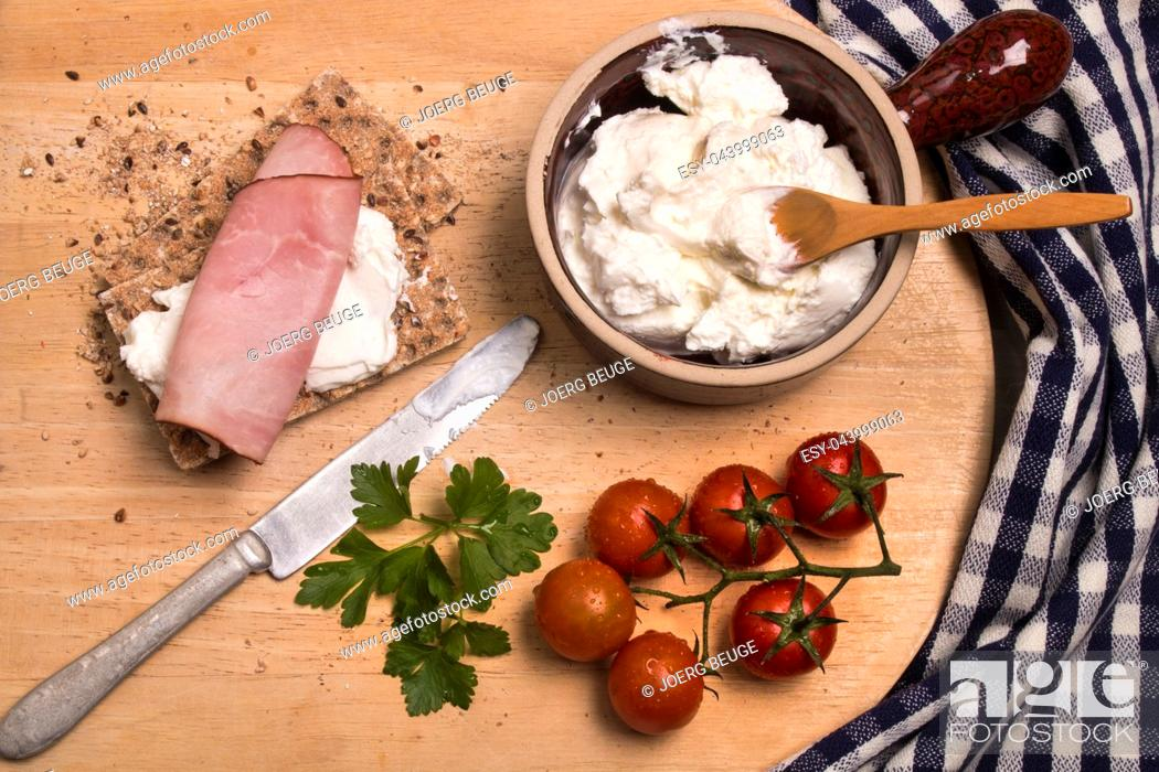Imagen: healthy breakfast with crispbread, quark, parsley and smoked ham on a wooden board.